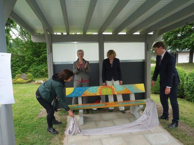 Die Künstlerin Beate Böhmke und Bürgermeister Claus Jacobi enthüllen die Trauerbank. Dahinter